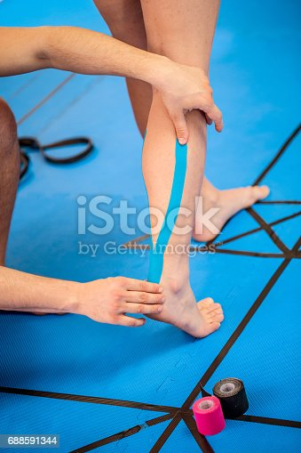 istock Physical Therapist Applying Kinesiology Tape To Woman Leg 688591344