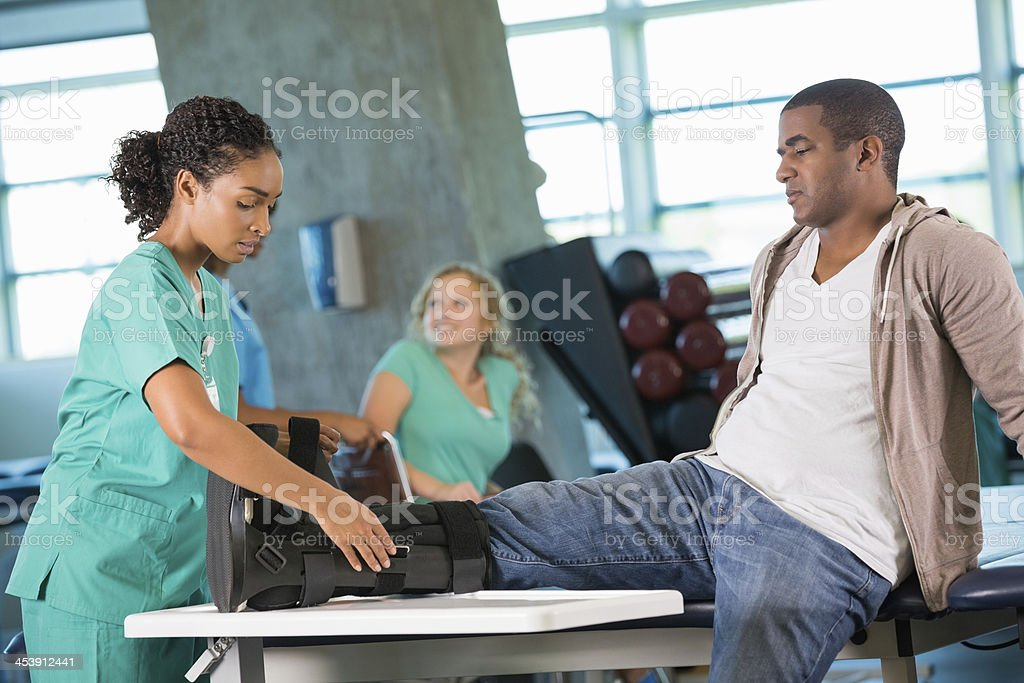 Physical therapist assisting injured patient in rehab gym stock photo