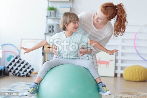 istock Physical therapist assisting little boy 875266340