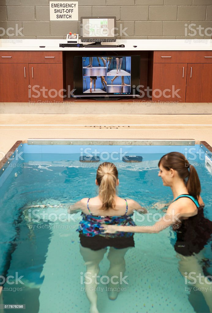 Physical Therapist Assisting Patient with Hydrotherapy in a Underwater Treadmill stock photo