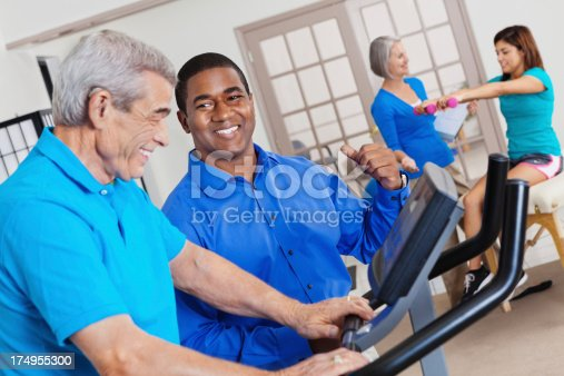912333752 istock photo Physical therapist assisting senior man with exercise equipment 174955300