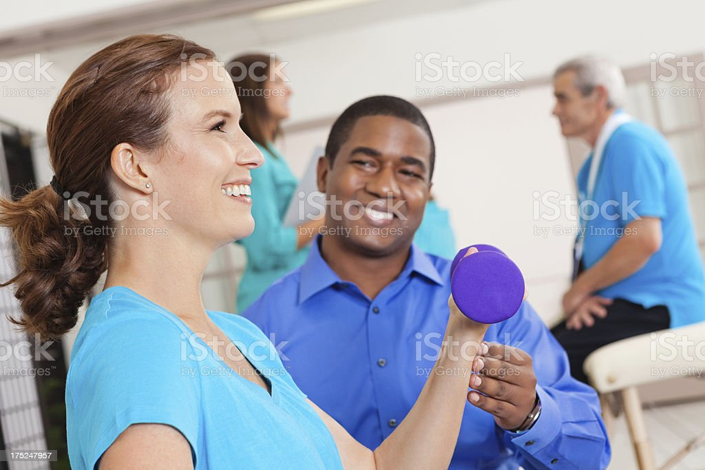 Physical therapist assisting woman with strength training at clinic royalty-free stock photo