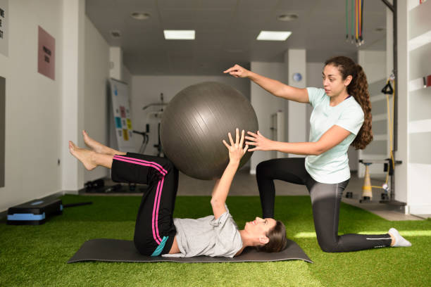 Physical therapist assisting young caucasian woman with exercise stock photo