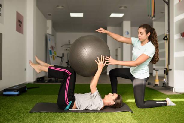 physiotherapeuten unterstützen junge kaukasischen frau mit übung - chiropraktik wellness stock-fotos und bilder