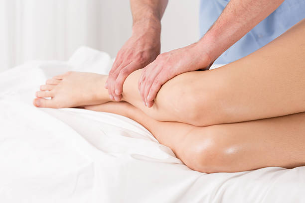 Physical therapist doing lymphatic drainage Physical therapist doing lymphatic drainage for the legs human leg stock pictures, royalty-free photos & images