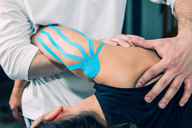 physical therapist doing shoulder treatment - sports medicine stock pictures, royalty-free photos & images