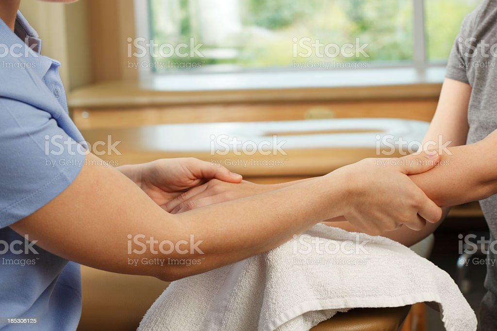 Physical therapist evaluating a patient's hand royalty-free stock photo