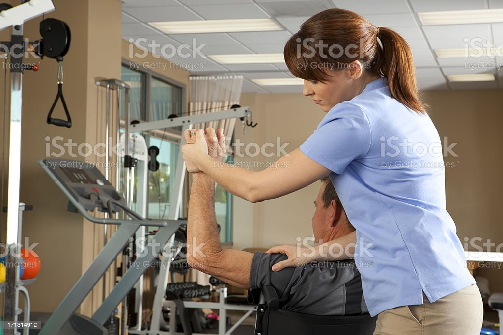 Physical therapist evaluating range of motion of patient in wheelchair royalty-free stock photo