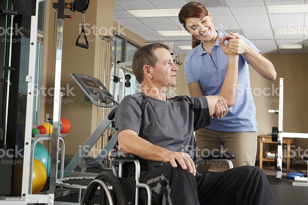 Fisioterapeuta evaluación del movimiento del paciente para silla de ruedas - foto de stock