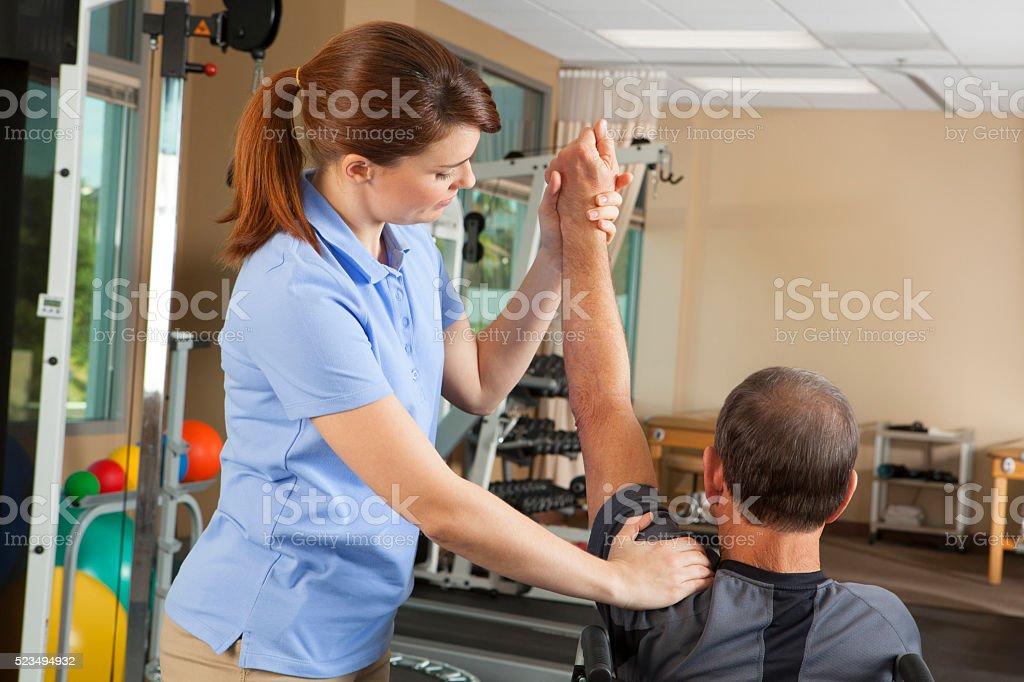 Fisioterapeuta evaluación de la amplitud de movimiento de pacientes para silla de ruedas - foto de stock
