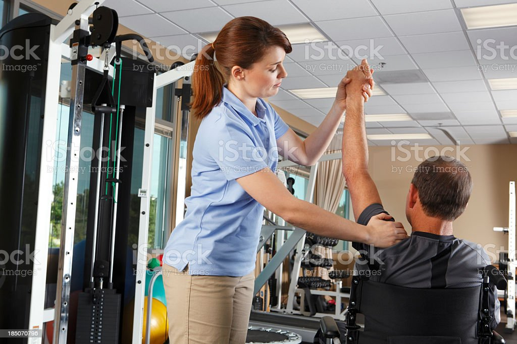 Physical therapist evaluating shoulder range of motion of patient in wheelchair royalty-free stock photo