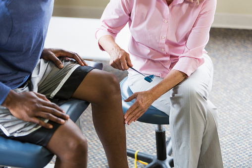 Cropped view of a female physical therapist examining a male, African American patient, testing his reflexes with a reflex hammer.  Focus is on the woman.