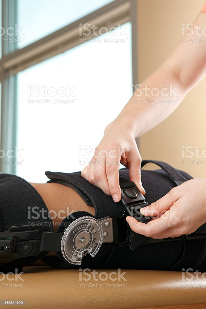Physical therapist fitting a patient with a knee brace stock photo