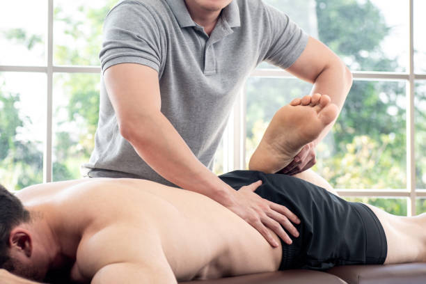physical therapist giving massage and stretching to athlete male patient - medicina sportiva foto e immagini stock