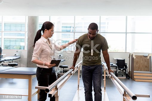 The female physical therapist guides the mid adult male military veteran as he walks on his foot during therapy.
