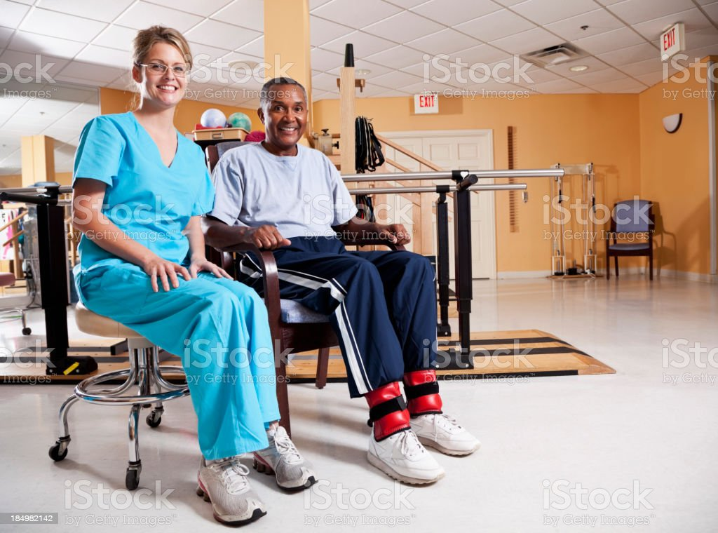 Physical therapist helping patient do leg strengthening exercise royalty-free stock photo