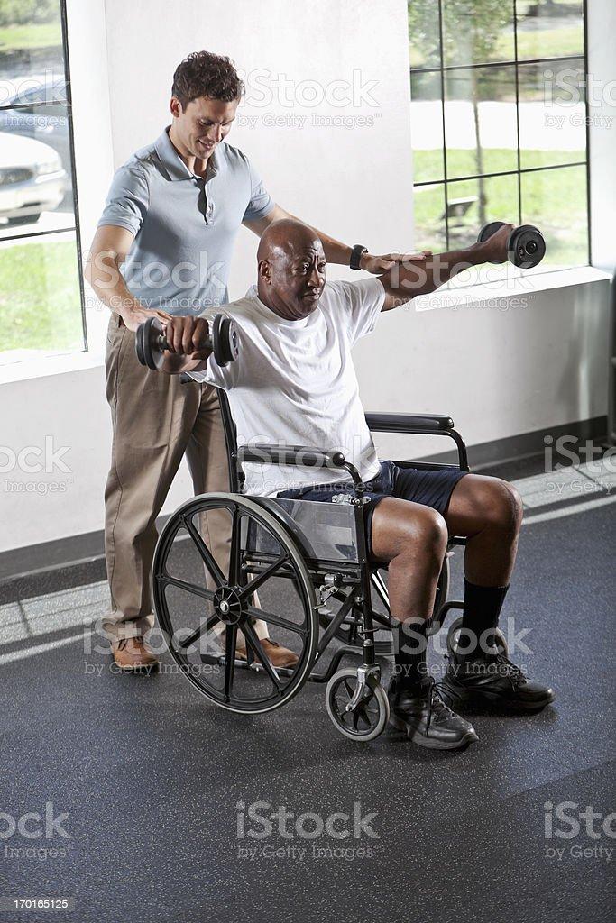 Fisioterapista aiutare paziente in sedia a rotelle - foto stock