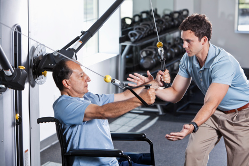 istock Physical therapist helping patient in wheelchair 170588274