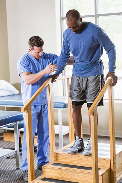 fisioterapeuta ajudando paciente em escadas - ortopedia - fotografias e filmes do acervo