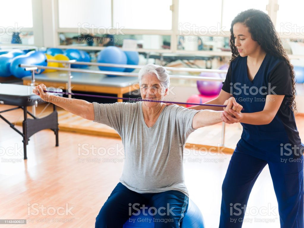Physical Therapist Helping Senior Woman To Stretch Stock Photo Download Image Now Istock