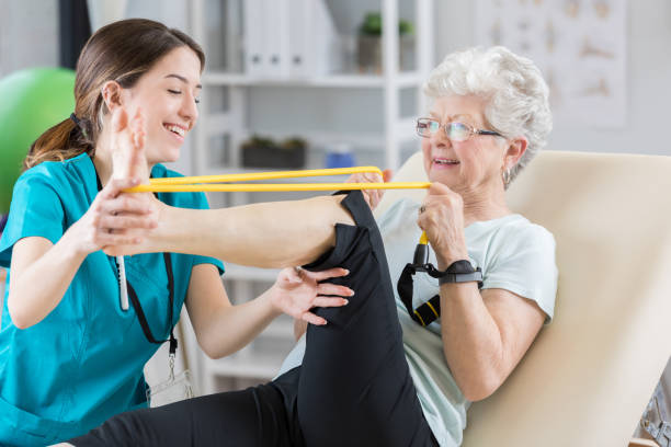 Physical therapist helps patient use resistance band Confident Caucasian female physical therapist helps senior Caucasian patient use resistance band. The woman is stretching out her leg. arthritis stock pictures, royalty-free photos & images
