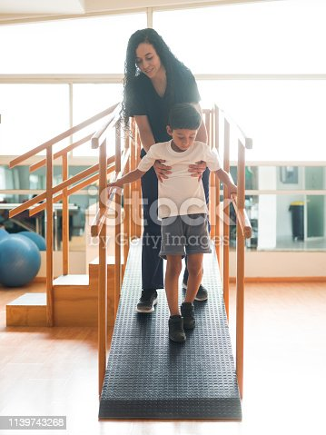 A female physical therapist holding a boy who is coming down a ramp during a physical therapy session.