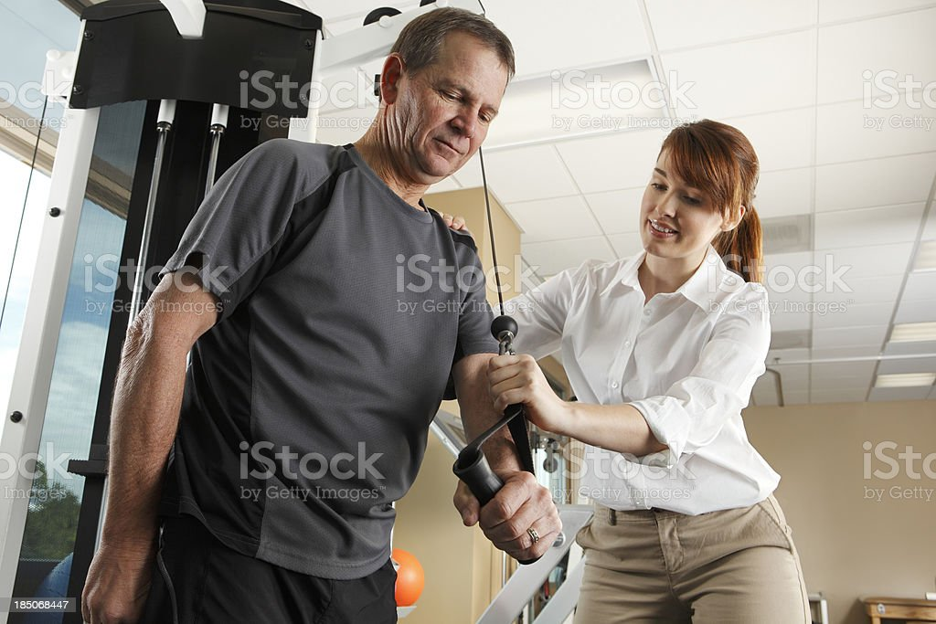 Physical therapist instructing man on proper use of exercise equipment royalty-free stock photo