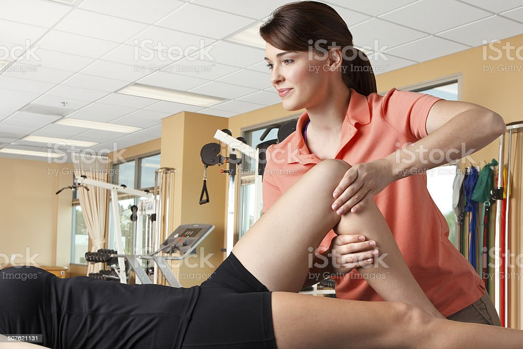 Physical therapist manipulating the knee of a female patient stock photo