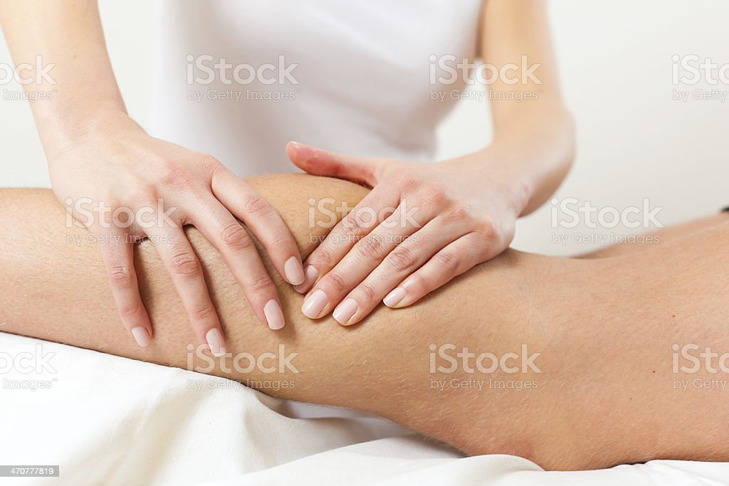 Physical therapist massaging calf stock photo
