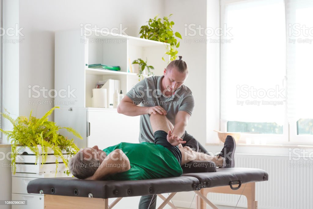 Senior man lying on bed in doctor's office, physical therapist...