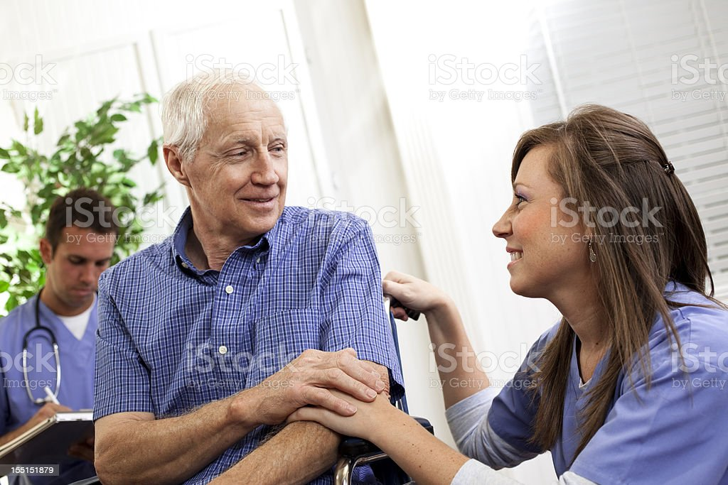 Physical therapist or nurse consoling senior man patient. Wheelchair. Doctor. royalty-free stock photo