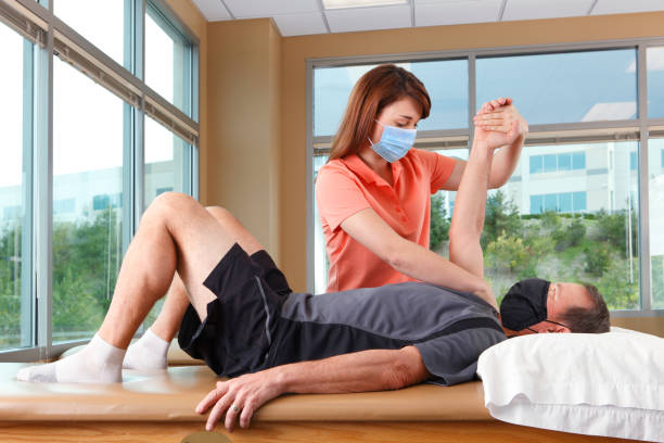 Physical Therapist Performing Shoulder PNF Pattern On Male Patient While Both Wear Protective Masks stock photo
