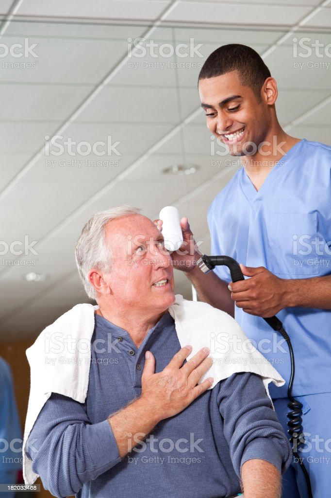 Physical therapist using ultrasonic massager on patient royalty-free stock photo