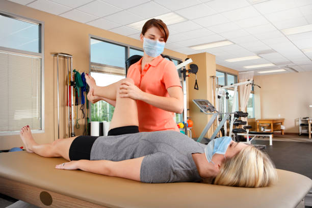 Physical Therapist Wearing Protective Face Mask Evaluates Range Of Motion stock photo