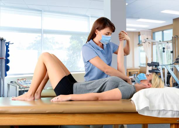 Physiotherapeut trägt Schutzmaske mit Schulter PNF-Muster auf weibliche Patientin auch tragen Schutzmaske – Foto