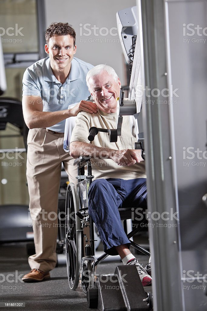 Physical therapist with patient in wheelchair royalty-free stock photo