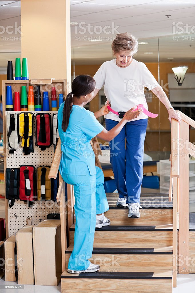 Physical therapist with senior woman climbing stairs royalty-free stock photo