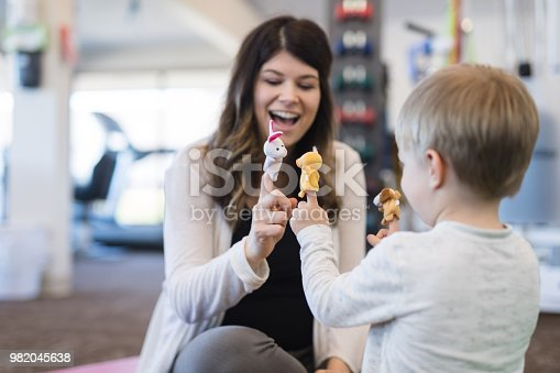 A therapist works with a young boy on a fun exercise where they are use finger puppets. They are sitting on the floor in the clinic. The shot is focused on her and is over his left shoulder.