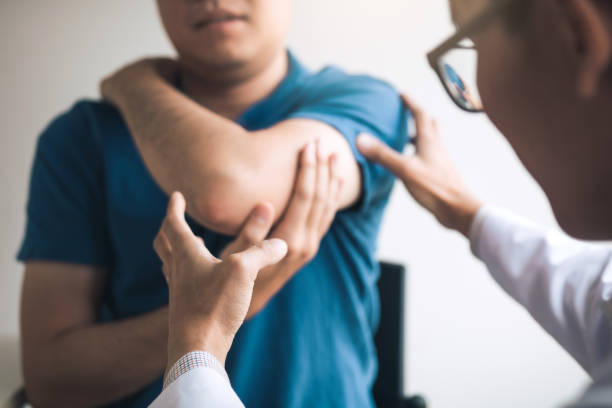 fisioterapeutas estão verificando pacientes cotovelos na sala de escritório da clínica. - articulação humana - fotografias e filmes do acervo