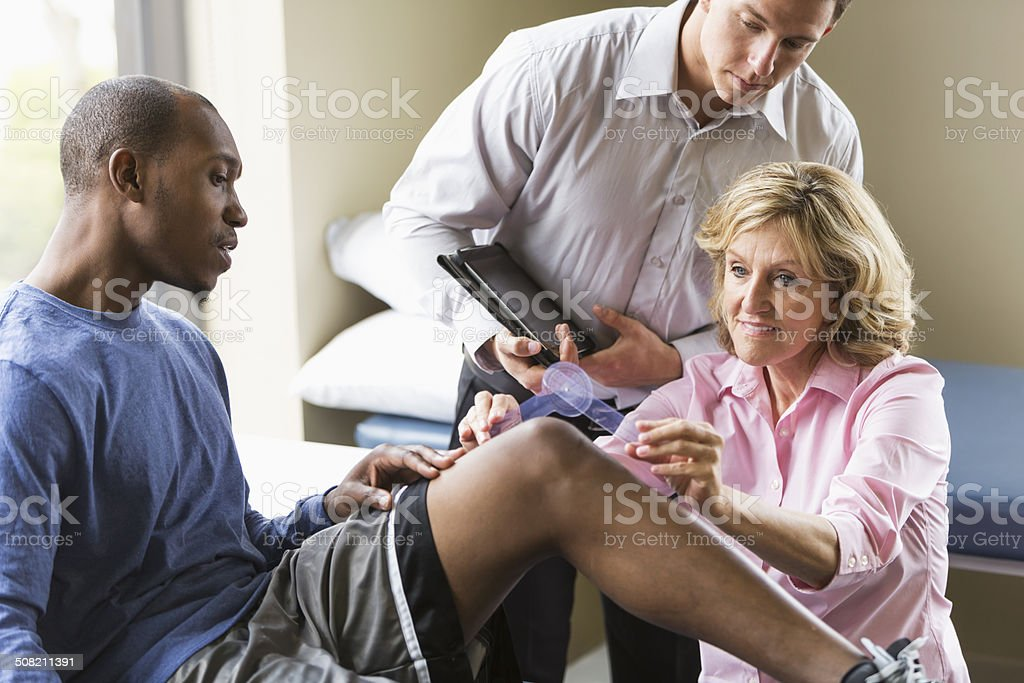 Physical therapists examining patient stock photo