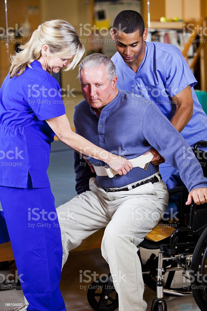 Physical therapists helping patient into wheelchair stock photo