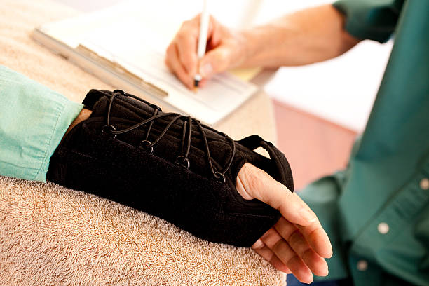 Physical therapy after wrist surgery. Arm brace. Therapist. stock photo
