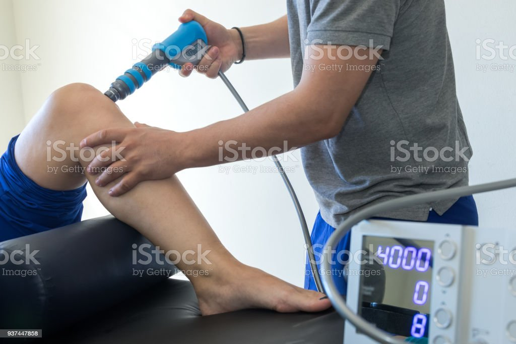 physical therapy of the knee and the foot with shock wave stock photo