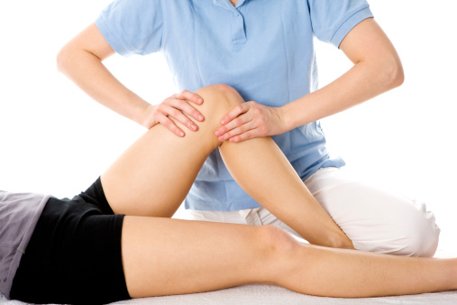 Close up showing a medical treatment of a young woman. A female physiotherapist is examining the leg of a young woman after a sports injury. Rehabilitation. Studio shot. High key. Isolated on white background. XXXL (Canon Eos 1Ds Mark III)