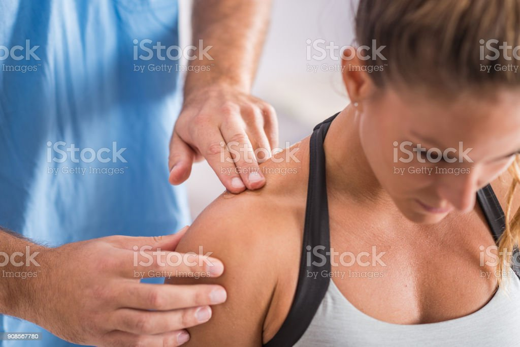 Physical therapy. Therapist addressing trapezius muscle stock photo