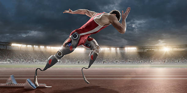 physically disabled athlete sprinting from blocks with artificial robotic legs - obstacle run stockfoto's en -beelden