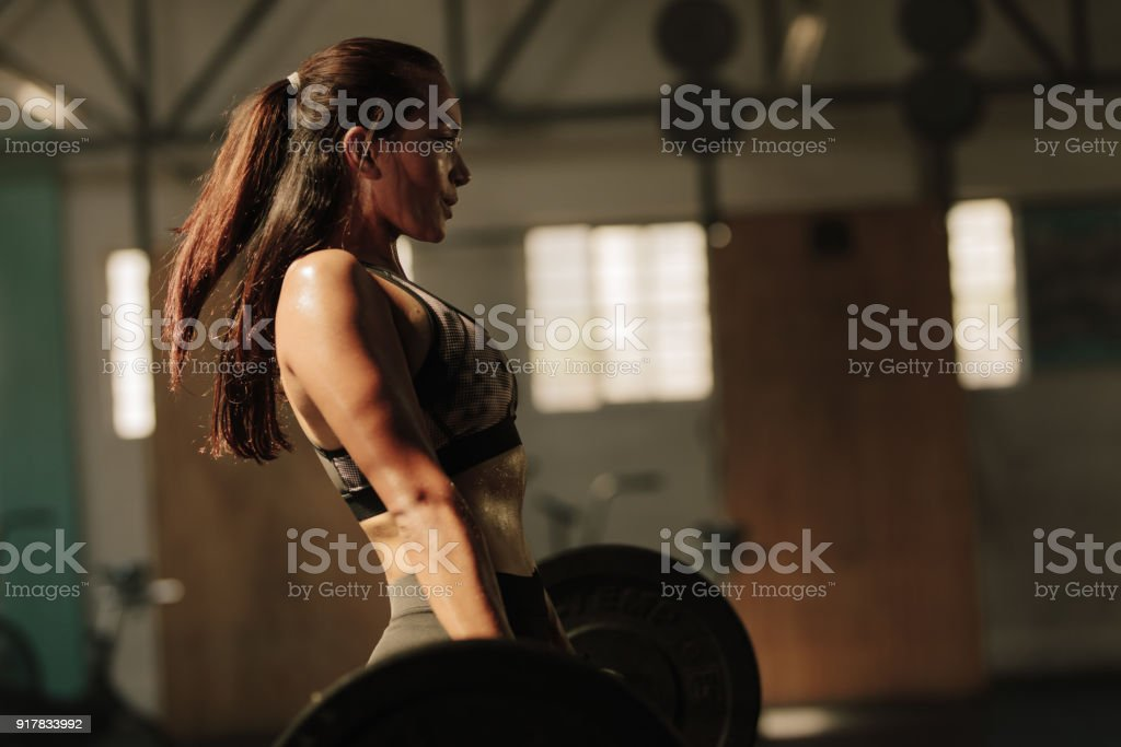 Physically fit woman lifting heavy weights stock photo