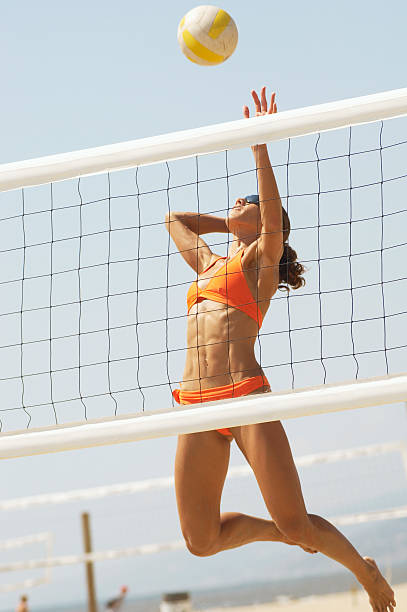 Physically Fit Young Woman Spiking Volleyball stock photo