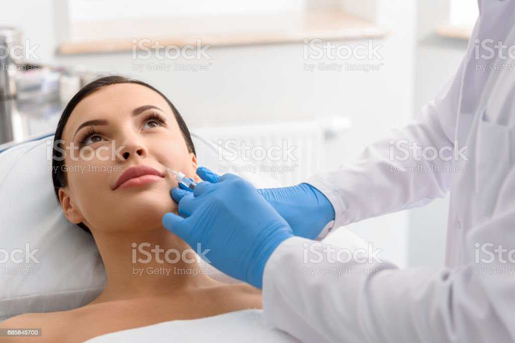 Physician administering liquid in skin of outgoing girl stock photo