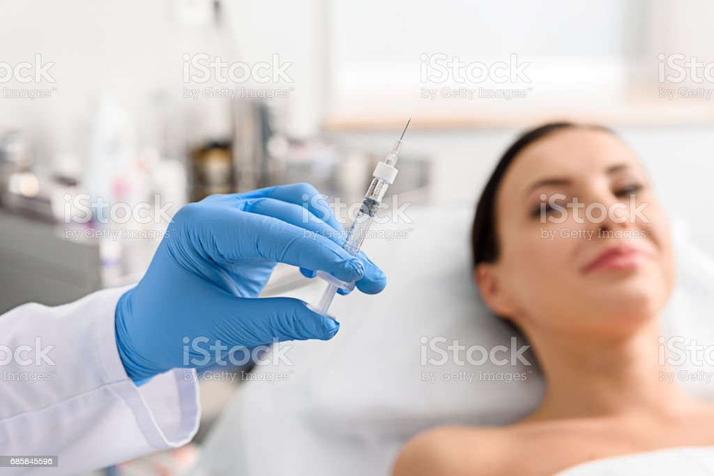Physician arm holding injector in cosmetology clinic - foto stock